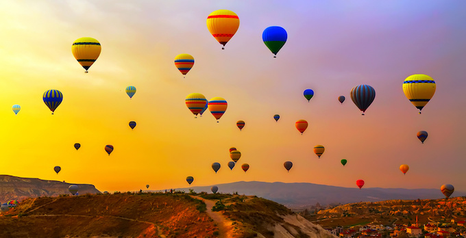 At sunrise with hundreds of different coloured air balloons in the sky