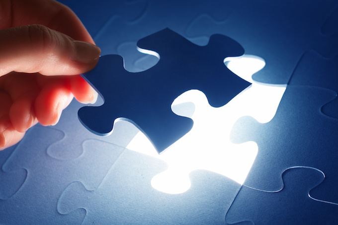 A hand putting the last piece of a puzzle together