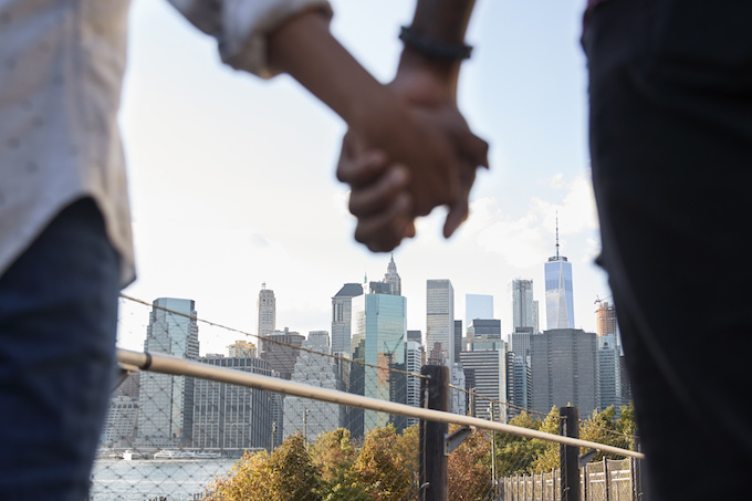 Man and women holding hands with skyline in the background
