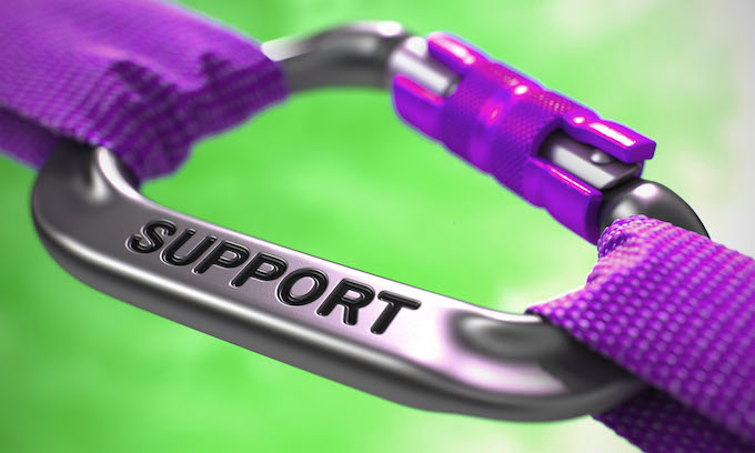 Purple straps held together with a purple carabiner with support printed on