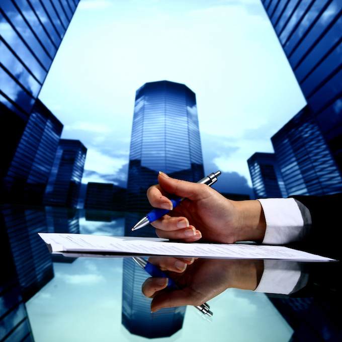 Office skyline in the background with a business person holding a pen