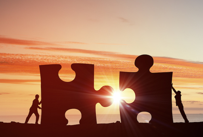 At sunrise, two people pushing two giant puzzle pieces together